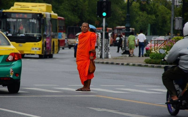 A Thai Monk stands in the middle of the cross walk waiting to get to the other side of the road - Bangkok, Thailand