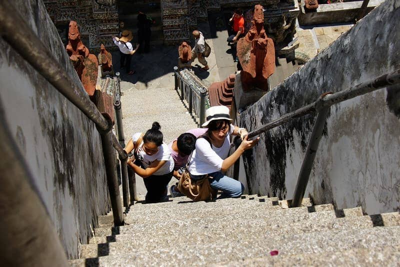 A group of ladies make their way up the impossibly steep Wat Arun - Bangkok, Thailand