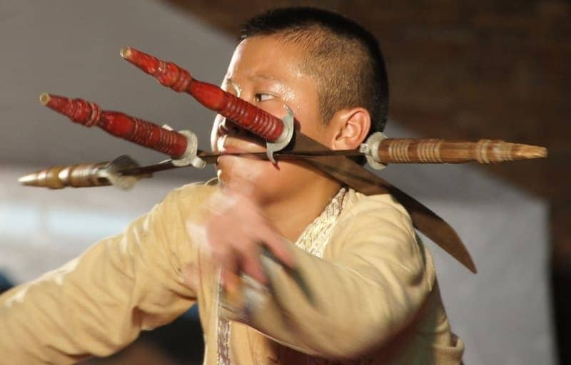 A Thai boy puts on a stunning display of theatrics by wielding a knife in his mouth during a performance in Chiang Mai, Thailand.