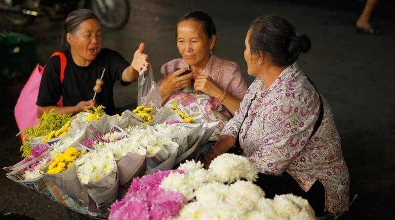 A group of Thai ladies engaging in conversation at a night bazaar in Chiang Mai, Thailand.