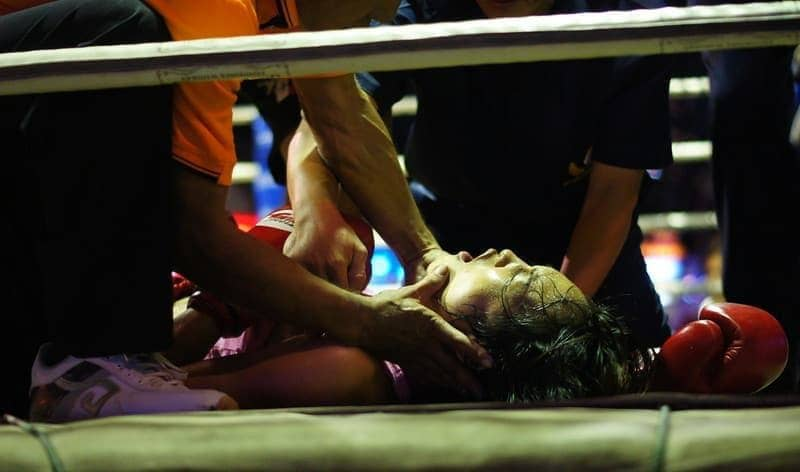 A female Muay Thai boxer surrounded by trainers gasps for breathe after being rendered unconscious