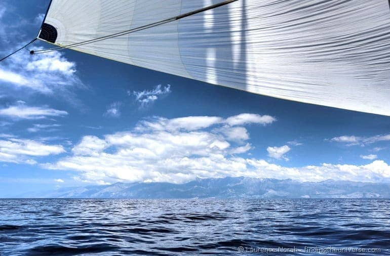 Blue sail sea sky mountains clouds