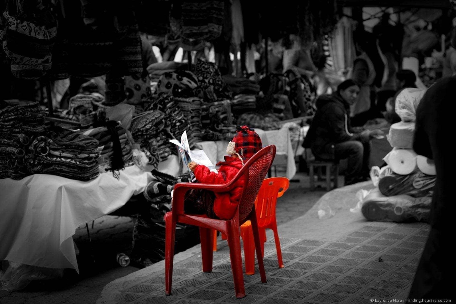 Boy reading paper Otavalo market Ecuador