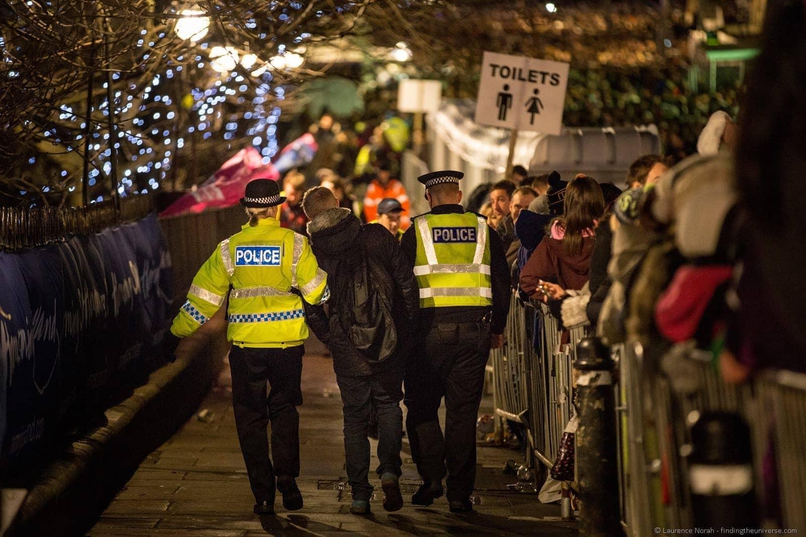 police escort drunken reveller away from hogmany new years edinburgh