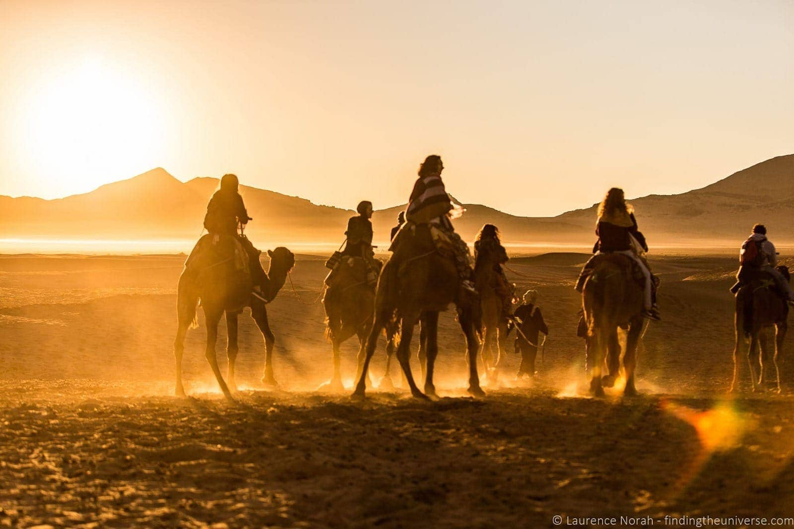Camels and riders in desert Morocco